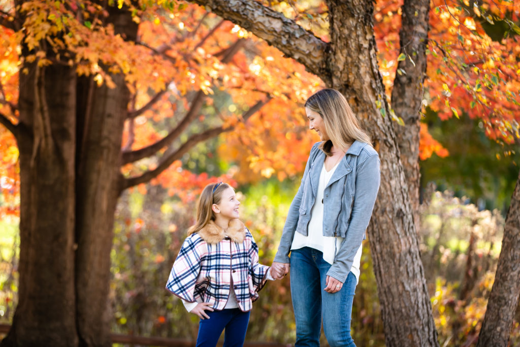Mom & daughter hold hands at Winnemac Park in Chicago in front of bright orange fall foliage